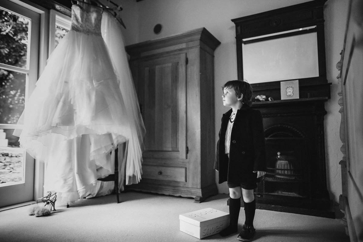 little boy looking at his mothers hanging wedding dress at ballybeg